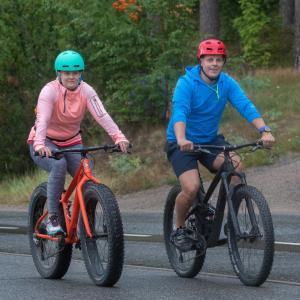 Mies ja nainen pyöräilevtä ulkona. Taustalle vihreitä lehtipuita.