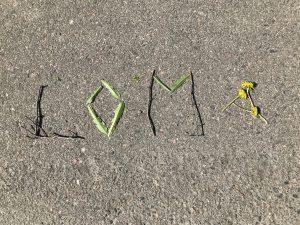 """Kepeillä ja heinillä kirjoitettu asfalttiin teksti """"Loma""""."""