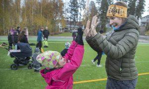 Nainen ja tyttö ovat jalkapallokentällä, hymyilevät ja lyövät kädet yhteen.