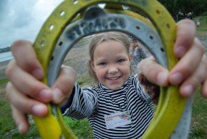Tyttö pitää kädessään hevosenkenkiä ja hymyilee.