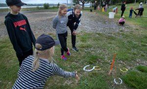 Lapset pelaavat pihapelejä kesällä ulkona.