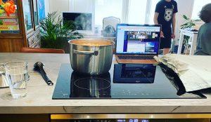 Kattila porisee hellalla, pöydällä on kannettava tietokone, jolla osallistutaan virtuaalilomalle. Taustalla kaksi poikaa leikkii.