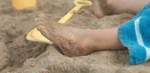 Lähikuva lapsen jalasta hiekkarannalla. Kuvituskuva.