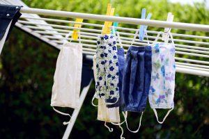 Värikkäitä kangasmaskeja roikkuu pyykkinarulla. Kuvituskuva.