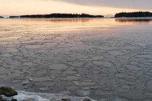 Talvinen merimaisema. Meren pinta on jäässä. Auringonlasku.