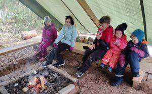 Lapset istuvat laavussa nuotion ääressä retkellä
