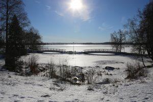 Keväinen talvimaisema. Maassa on lunta, aurinko paistaa. Kuvituskuva.